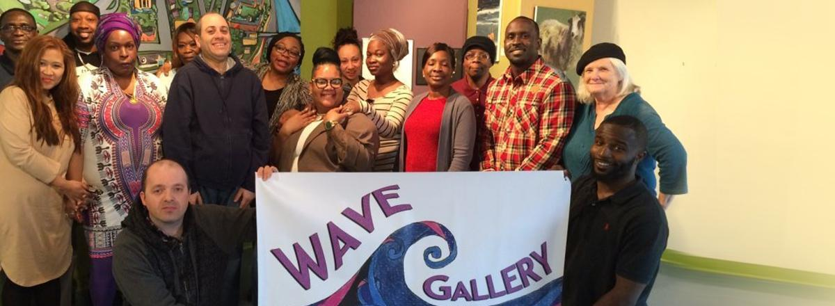 Wave art gallery, crowd of artists holding a sign in fornt of them