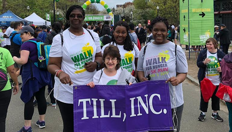 Walk for hunger participants holding a purple banner