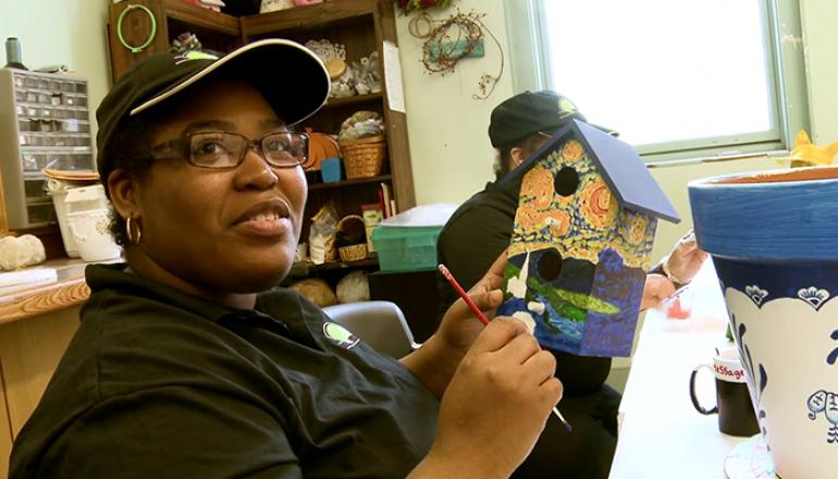 ETC crafts, a woman painting birdhouse